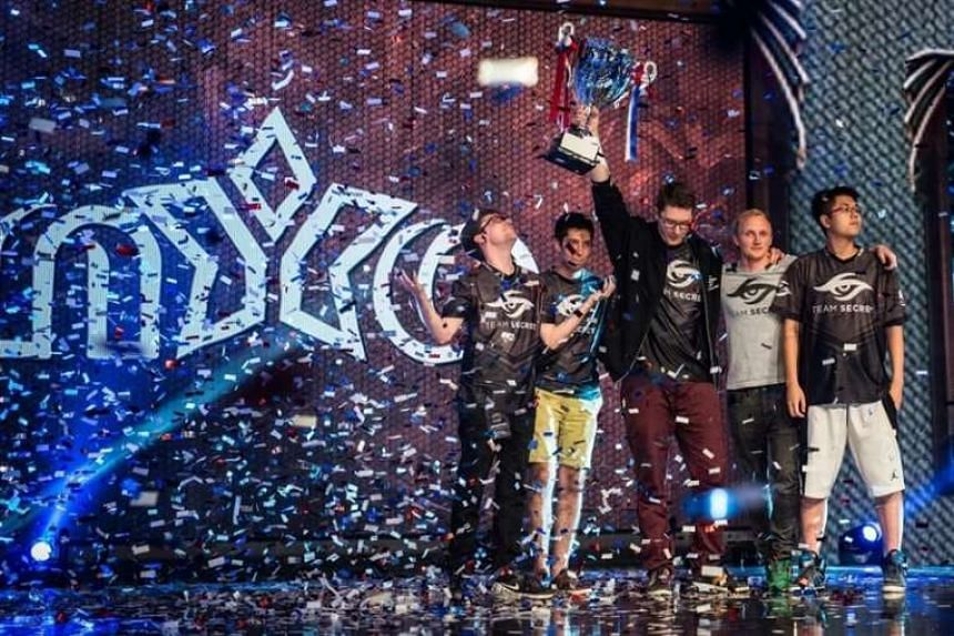 """Team Secret's captain, Clement """"Puppey"""" Ivanov, holds up the Nanyang Dota 2 Championships trophy after their victory."""