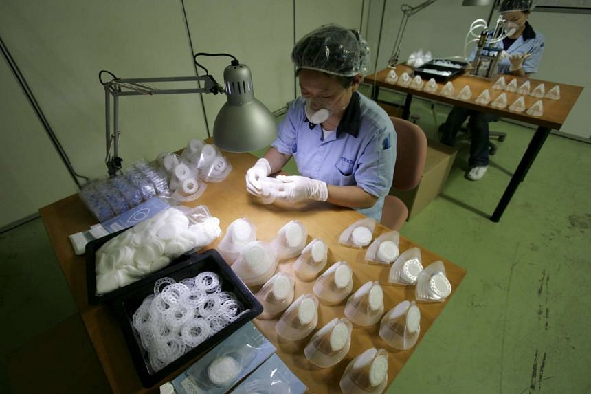 Workers assemble protective masks at a manufacturing facility in Singapore in this May 4, 2009, file photo.