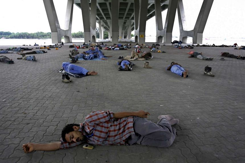 Construction workers sleeping under an expressway bridge during their lunch break in Singapore.