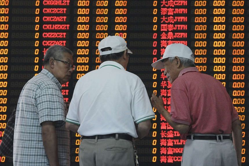 Investors talk in front of an electronic board showing stock information at a brokerage house in Shanghai.