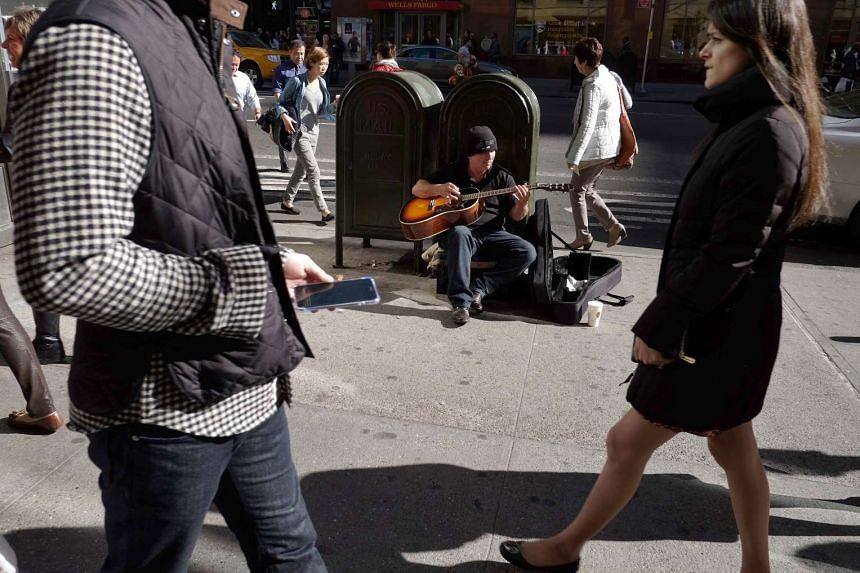 A man plays a guitar on a New York street hoping for donations from locals.