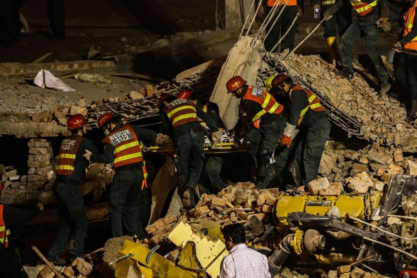 Rescue workers recover a body amid rubble of a factory that collapsed in Lahore, Pakistan, Nov 4.