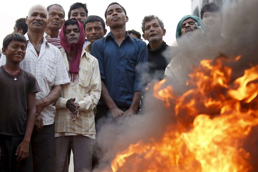 Protesters burn a tyre to block the highway connecting Nepal to India during a strike on Nov 5, 2015.