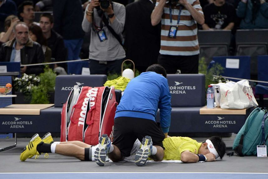 A member of the medical team attends to Japan's Kei Nishikori before he retired.