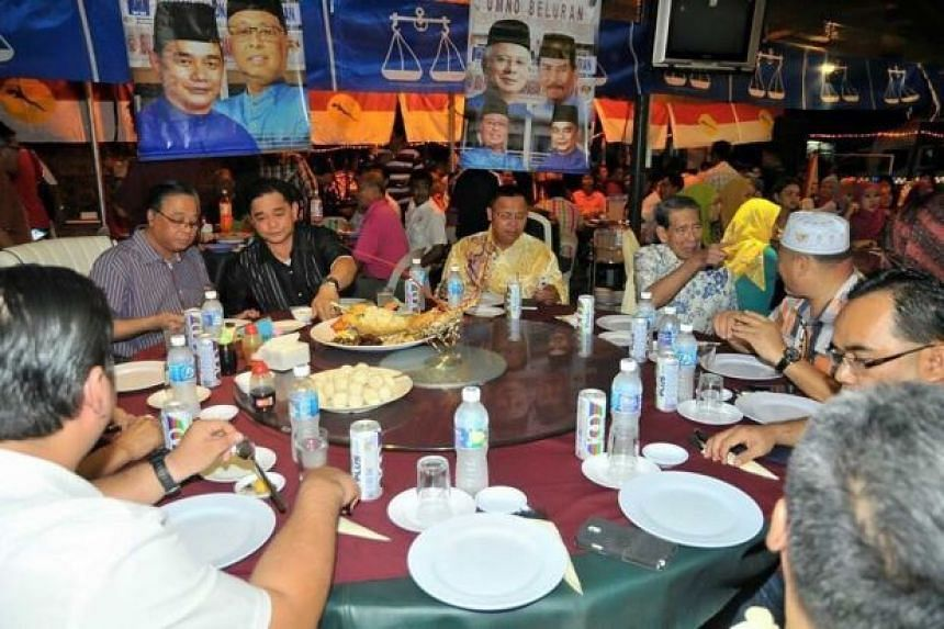 Malaysian minister Ismail Sabri Yaakob (left, in striped shirt) and Beluran Umno chief James Ratib (in black) with the turtle eggs on the table in front of them.