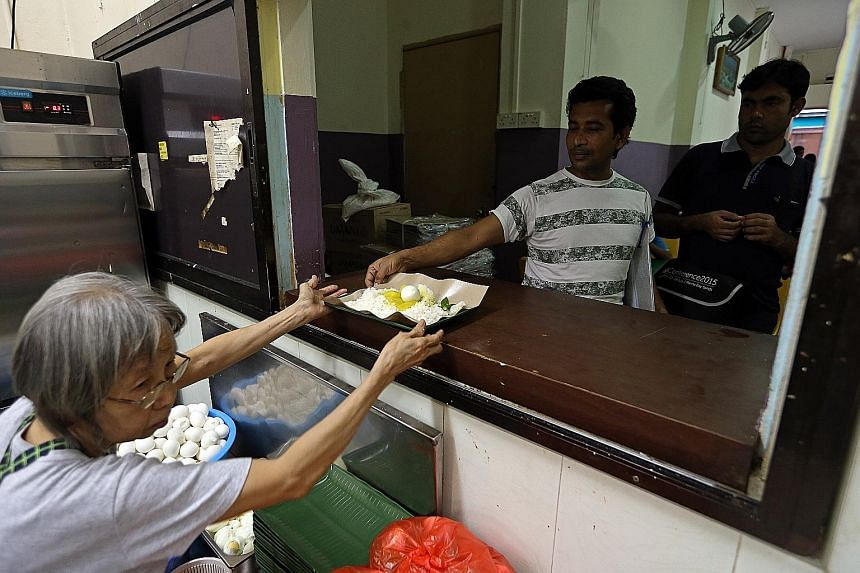 South Asian migrant workers collecting their free meals from the kitchen at Isthana Restaurant in Rowell Road, under a project by TWC2.