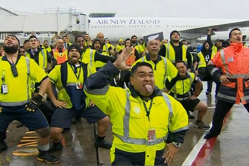 From far left: Auckland airport workers honouring the All Blacks with a Maori war dance, or haka, on the tarmac in heavy rain yesterday. All Blacks captain Richie McCaw holding the Webb Ellis Cup during a victory parade at Victoria Park.