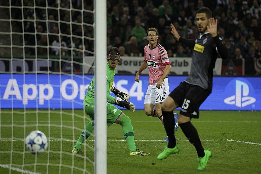 Stephan Lichtsteiner (in pink) sends the ball past hosts Moenchengladbach's goalie Yann Sommer (left) for his first Champions League goal.