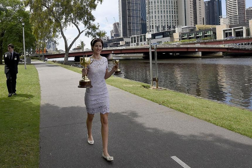 """Australian Michelle Payne with the Melbourne Cup trophy yesterday, a day after she became the first female jockey to win the 154-year-old """"race that stops a nation"""" when she rode outsider Prince of Penzance at Flemington. Despite this success, women"""