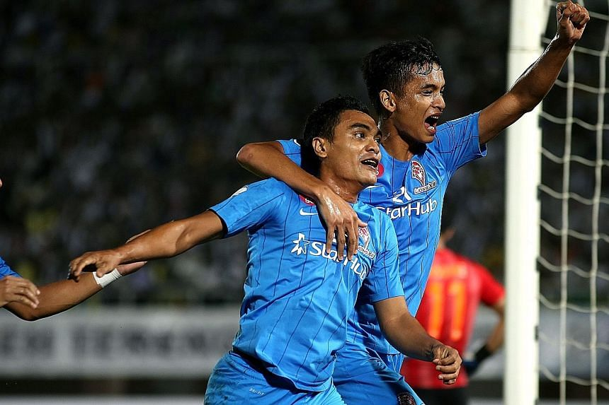LionsXII substitute Sufian Anuar (left) and Safuwan Baharudin celebrating his equaliser after just coming on for Khairul Amri. Torrential rain and a waterlogged pitch halted play for half an hour just past the hour mark.