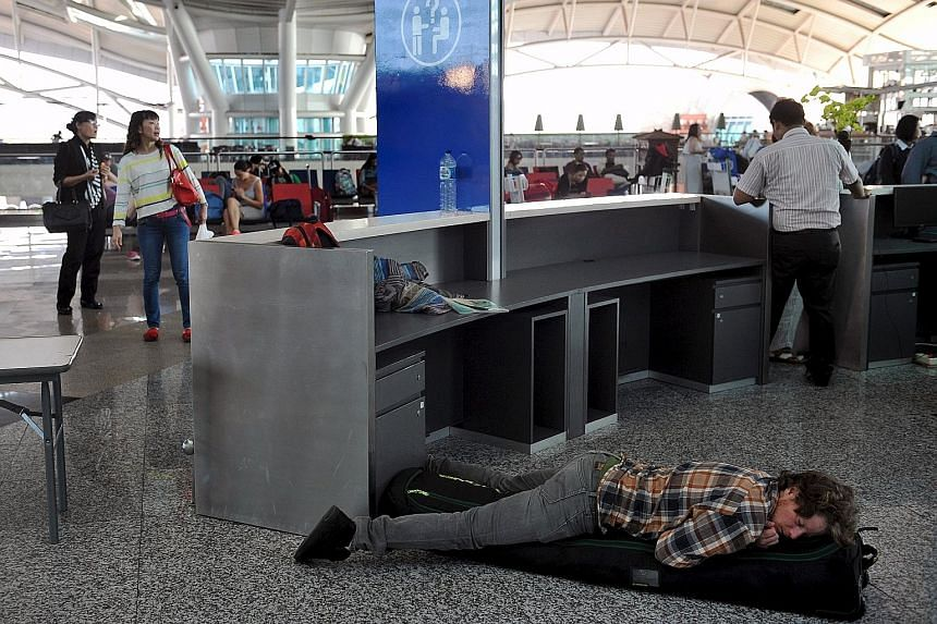 A traveller catching some shut-eye yesterday at Bali's Ngurah Rai airport in this picture from Antara Foto. Nearly 700 flights have been cancelled, said the Bali airport authorities, because of a large ash cloud from Mount Rinjani on nearby Lombok is