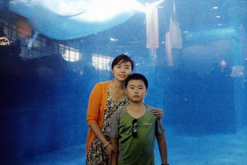 Ms Zhang Huanli, 33, who works in estate management, with her son Shen Ben, 13.