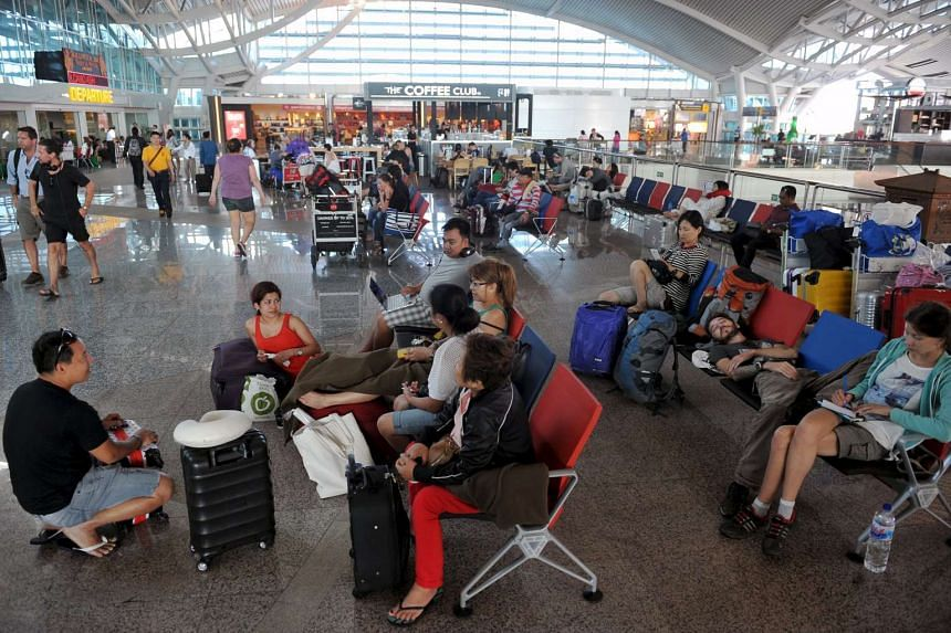 Passengers spent their time at a waiting room as all flights were cancelled at the Ngurah Rai airport in Bali, on Nov 4, 2015.