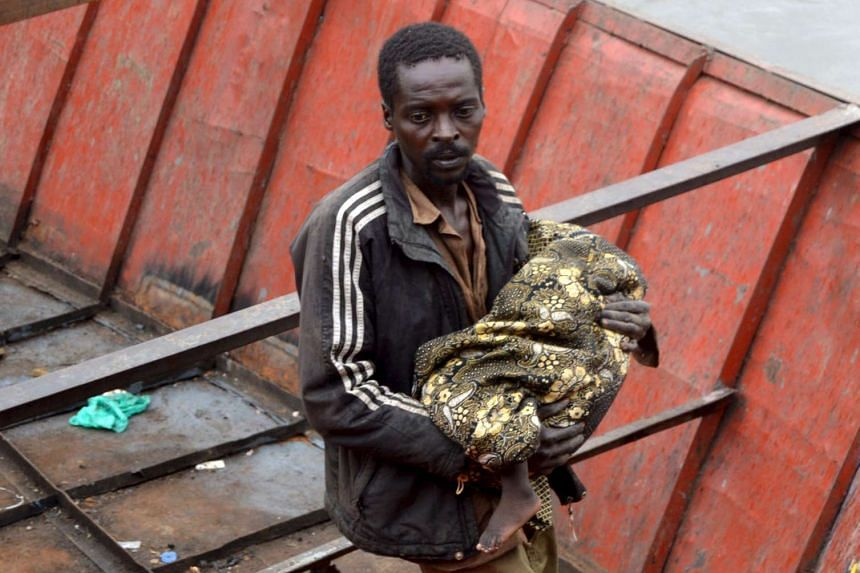 A rescuer carries Nyloak Tong, a fourteen-month-old girl who survived the cargo plane crash.