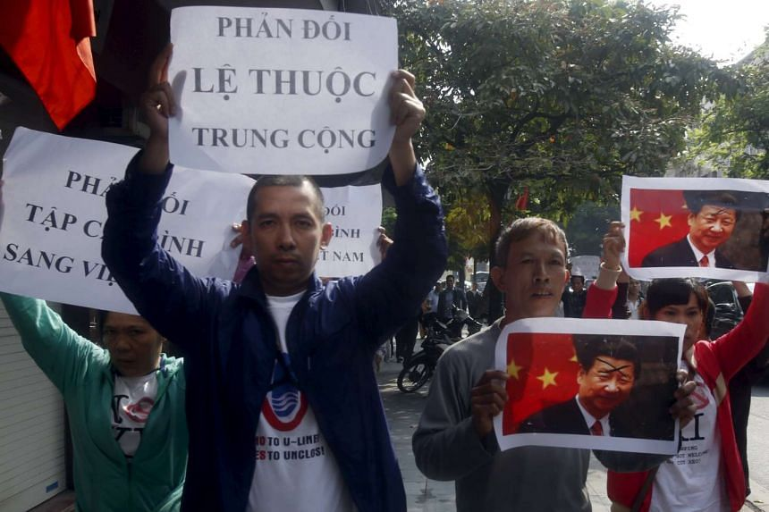 Protesters in Hanoi holding images of Chinese President Xi Jinping and anti-China signs during a protest on Nov 3, 2015, ahead of his visit to Vietnam.