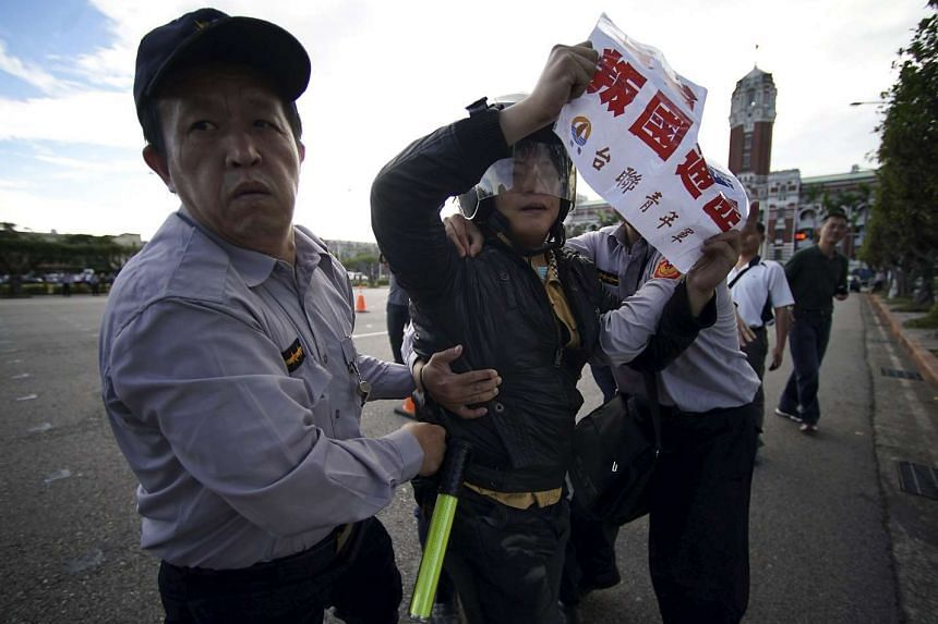 Police officers drag an activist protesting against the upcoming Singapore meeting between Taiwan's President Ma Ying-jeou and China's President Xi Jinping, in front of the Presidential Office in Taipei, Taiwan, Nov 4, 2015.