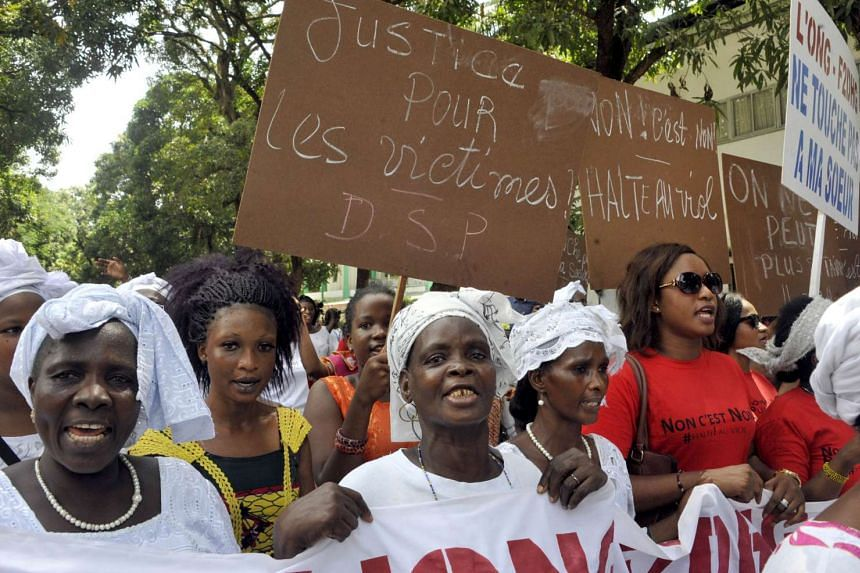 """Placards read """"Justice for the victims"""" and """"Stop rape - no means no"""" during a protest against violence towards women in Conakry."""