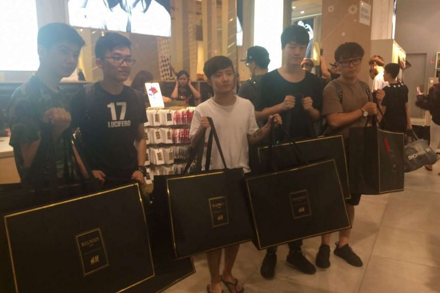 Shoppers with their Balmain x H&M collection purchases.