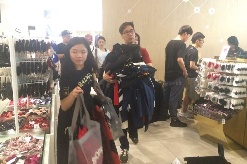 Shoppers getting their hands on the Balmain x H&M collection at H&M Orchard Building.
