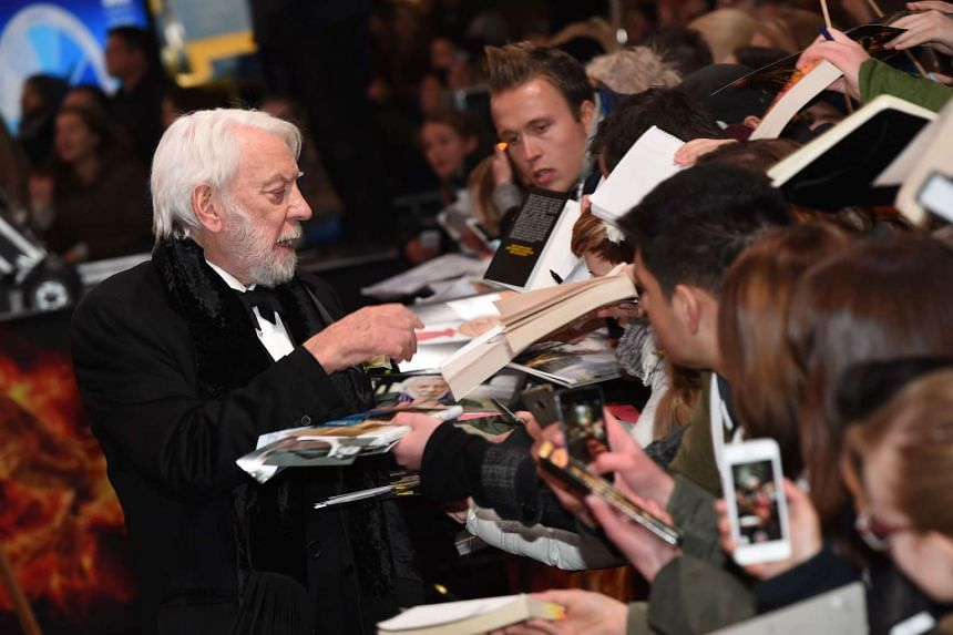 US actor Donald Sutherland signing autographs for fans as he arrives for the world premiere of the movie The Hunger Games: Mockingjay — Part 2, in Berlin on Nov 4, 2015.