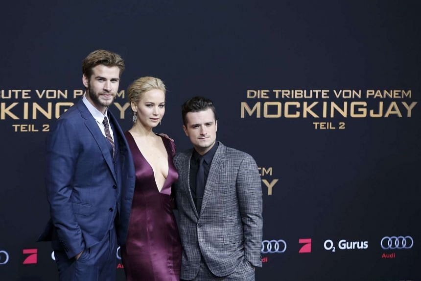 (From left) Liam Hemsworth, Jennifer Lawrence and Josh Hutcherson posing as they arrive for the world premiere of The Hunger Games: Mockingjay - Part 2 in Berlin, Germany, on Nov 4, 2015.