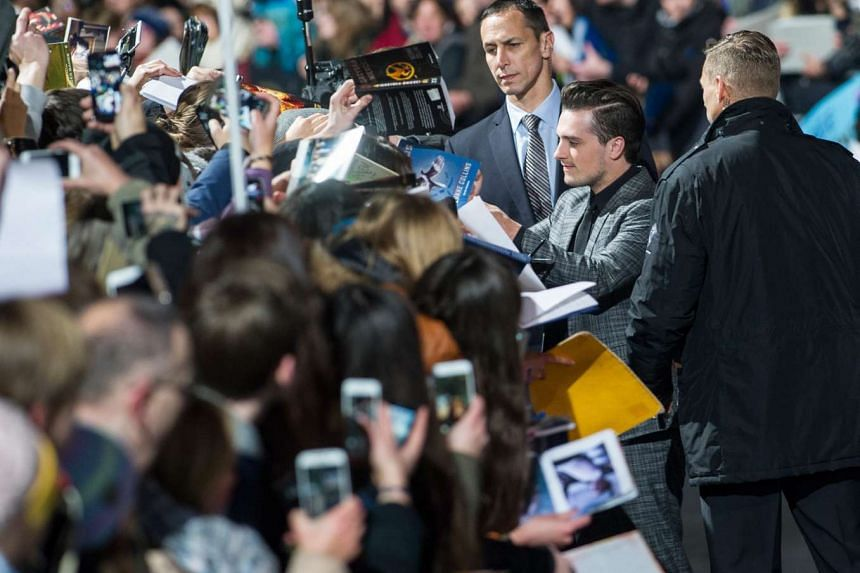 Josh Hutcherson (centre) signing autographs as he arrives for the world movie premiere of Hunger Games: Mockingjay - Part 2, at the Cinestar-Kino in Berlin, Germany, on Nov 4, 2015.