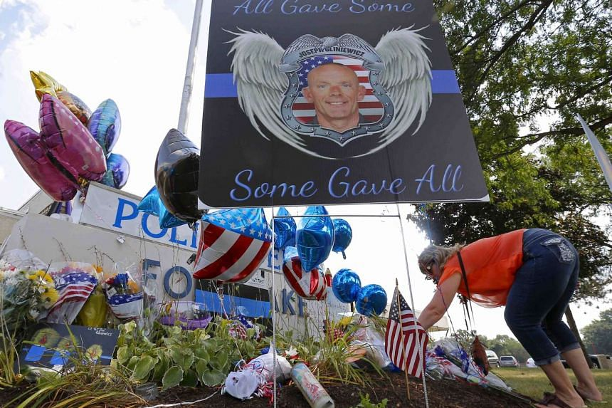 A woman laying flowers at a vigil for US police officer Charles Joseph Gliniewicz in Fox Lake, Illinois, on Sept 2, 2015.