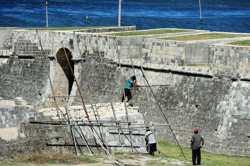 Sri Lankan labourers work on the ramparts and moat in front of the 17th century Dutch-built Jaffna fort that is undergoing restoration in the northern city of Jaffna.