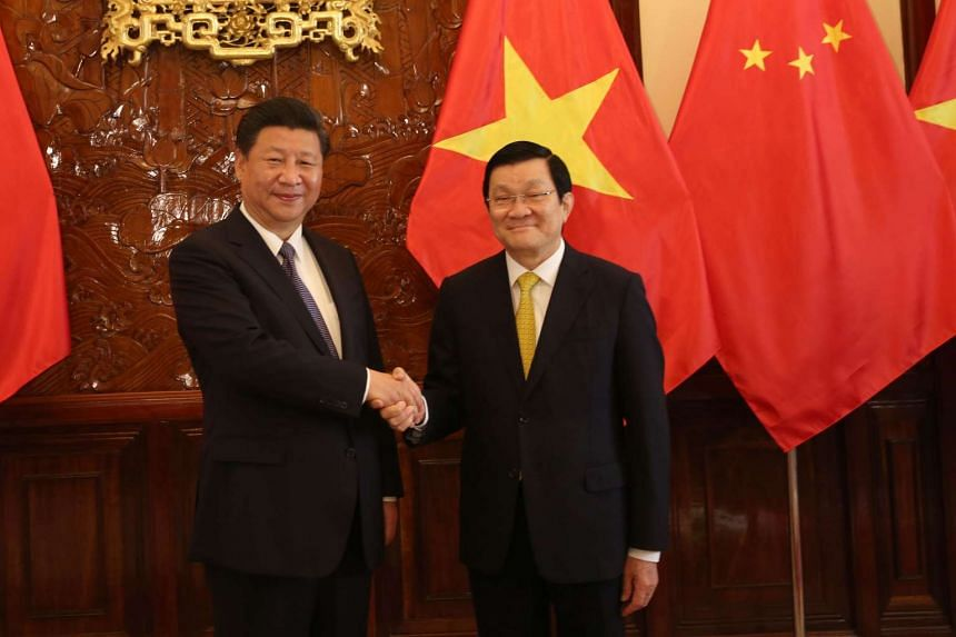 Chinese President Xi Jinping (left) and Vietnamese President Truong Tan Sang shake hands before a meeting at the Presidential Palace in Hanoi on Nov 6, 2015.