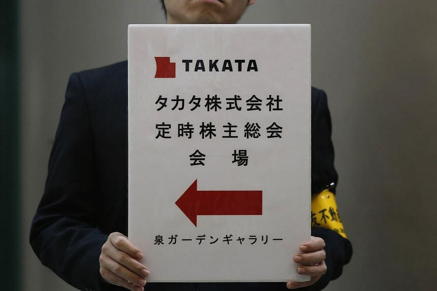 A Takata employee holding a signboard for the company's Annual General Meeting in Tokyo in 2014.