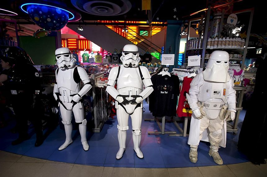 People dressed as Storm Trooper characters standing in front of toys that went on sale at midnight in advance of the film Star Wars: The Force Awakens in Manhattan, New York.