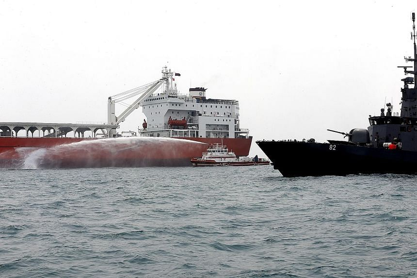 "An SCDF maritime fire vessel dousing the FK Avatar cargo vessel (far left) with water after a patrol craft from the navy first alerted multiple agencies under the SMCC to the presence of ""hijacking"" activities."
