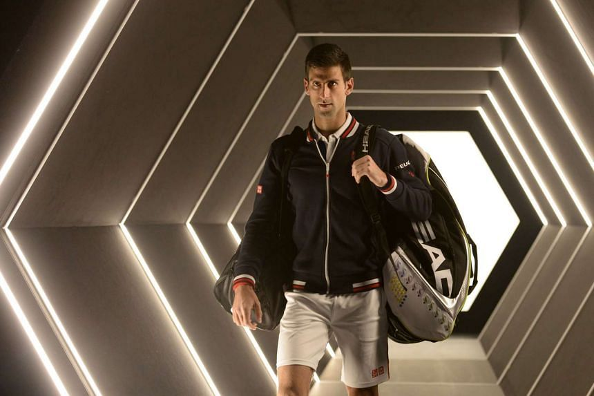 Djokovic arrives on court for his third round tennis match against France's Gilles Simon.