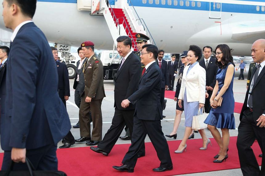 Chinese President Xi Jinping (centre, left) and his wife Peng Liyuan (in white jacket) walk along the red carpet at Changi Airport accompanied by Finance Minister Heng Swee Keat and his wife.