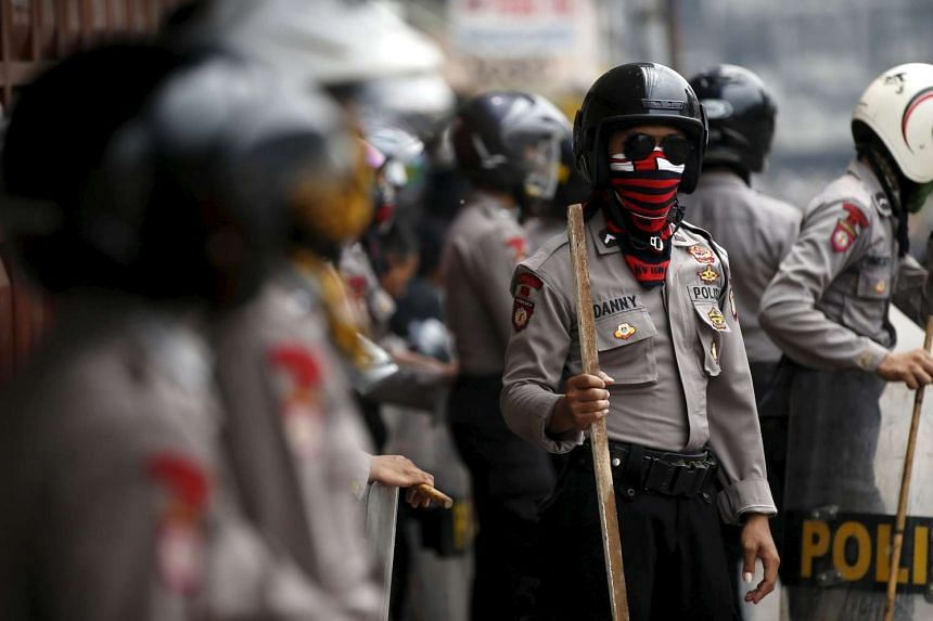 Indonesian policemen standing guard on a street after clashing with residents in Jakarta on Aug 20, 2015.