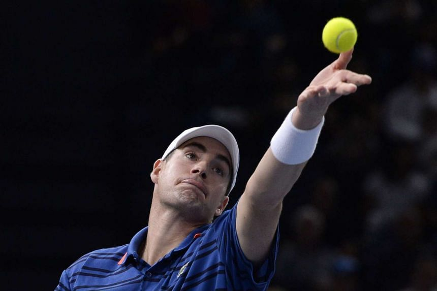 Isner serves the ball to Federer during their third-round match.