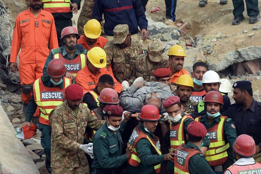 Rescuers evacuating a man pulled from under the rubble of the collapsed factory on the outskirts of Lahore yesterday. Soldiers and rescuers were carefully cutting through steel and using cranes to lift the debris of the building, in a bid to find peo