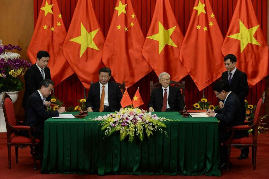 Chinese President Xi Jinping (centre left) and Vietnam Communist Party Secretary General Nguyen Phu Trong (centre right) witness a signing ceremony of a dozen bilateral agreements in Hanoi on Nov 5, 2015.