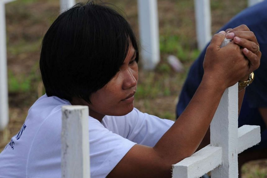 Juvelyn Luana, who lost her husband and four children at the height of super typhoon Haiyan, prays at a mass grave for victims in Tacloban on Nov 1.
