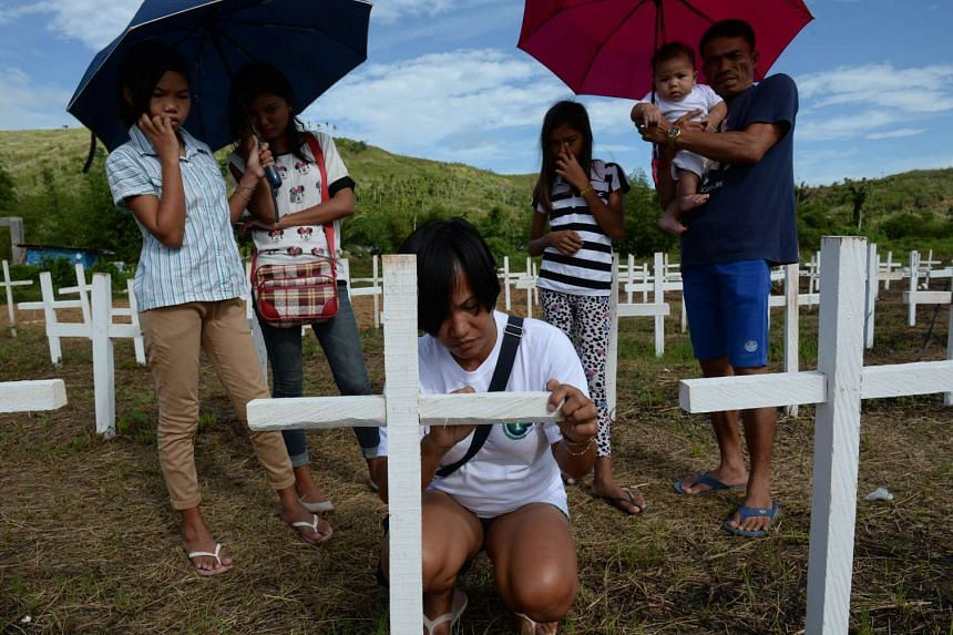 Typhoon Haiyan survivor Juvelyn Luana (front) writing the names of her dead loved ones on a cross at a mass grave in Tacloban on Nov 1, while her partner Joel holds their new baby Jacob (right), and step daughters look on.