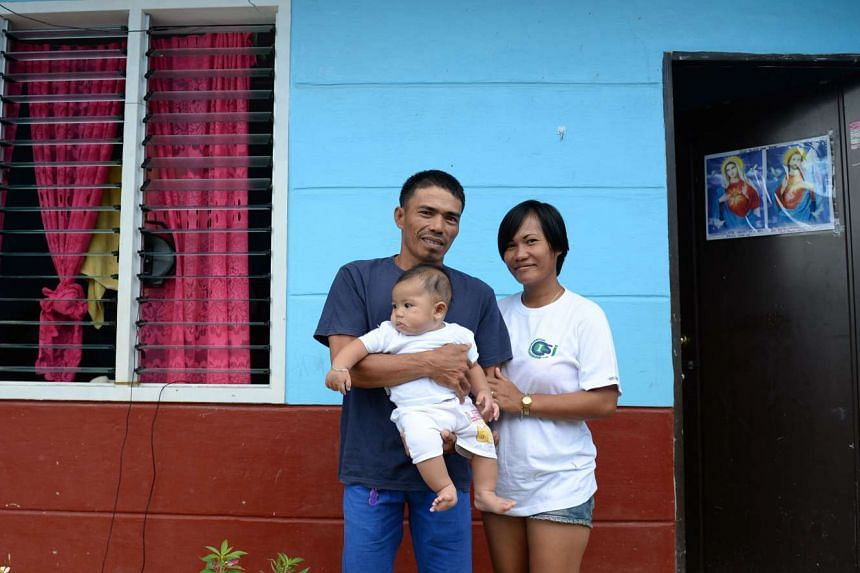 Typhoon Haiyan survivor Juvelyn Luana (right) with her partner Joel and their baby Jacob in front of their new house at a resettlement site in Tacloban on Nov 1.