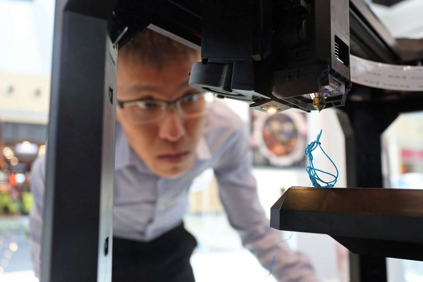 A man observing a 3D printer in action. 3D printing is among the areas that ST Engineering will invest in.