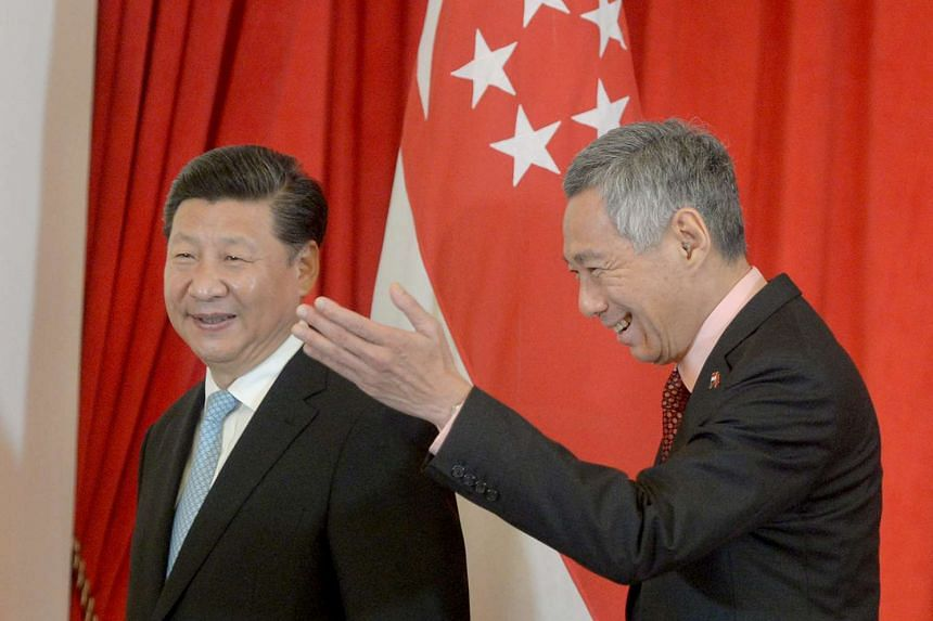 PM Lee Hsien Loong gesturing to China's President Xi Jinping after the signing of MOUs between China and Singapore.