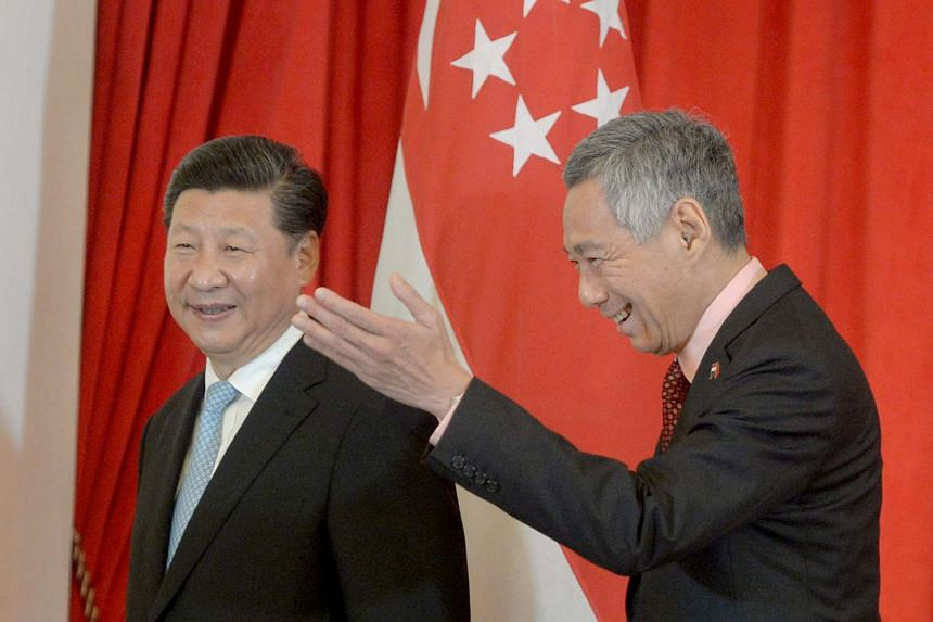 PM Lee Hsien Loong (right) gesturing to China's President Xi Jinping after the signing of MOUs between China and Singapore on Nov 7, 2015.
