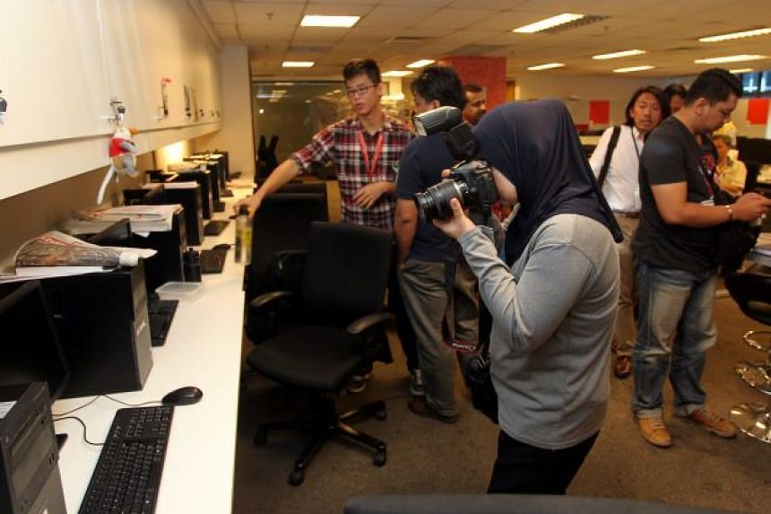 Policemen and the Malaysian Communication and Multimedia Commission at The Star's office.