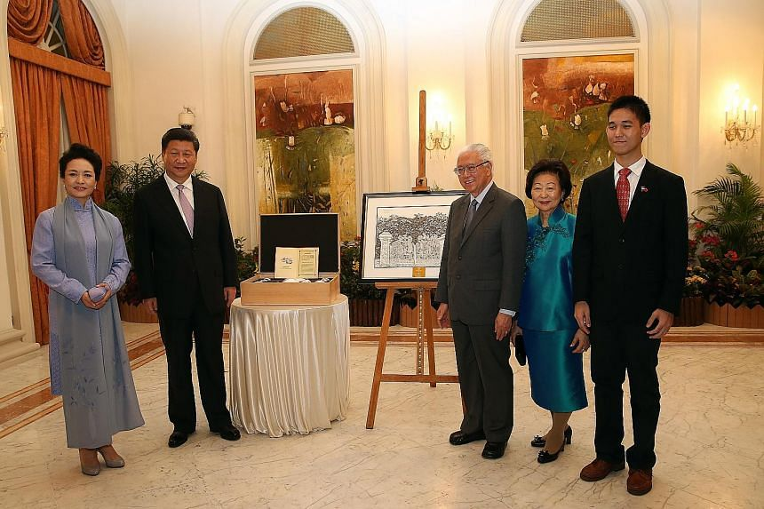 (From far left) Madam Peng Liyuan, President Xi Jinping, President Tony Tan, his wife Mary and Pathlight student Glenn Phua who did the drawing. (Above) The tea and coffee set presented to Dr Tan.
