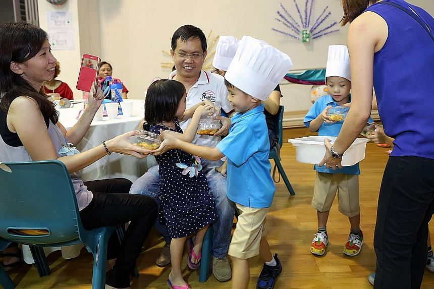 Tan Yi Hang (centre), six, handing a box of rojak to his mother at the graduation ceremony in Punggol View Primary School. About 100 children, their parents and teachers gathered to celebrate the completion of their pre-school education.