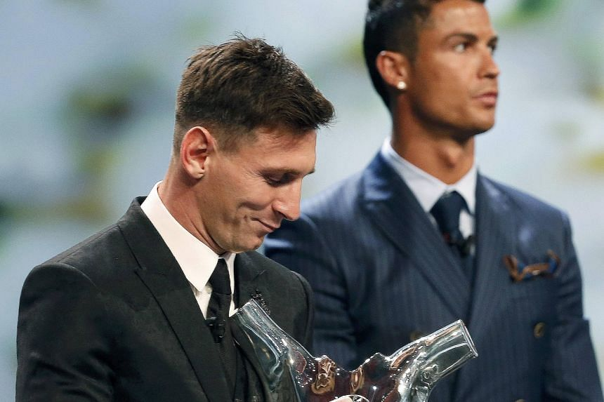 Barcelona's Lionel Messi (left) receiving his trophy after being named Uefa's best player in Europe for the 2014-2015 season on Aug 27. He had beaten Cristiano Ronaldo (right) and Luis Suarez to the honour.