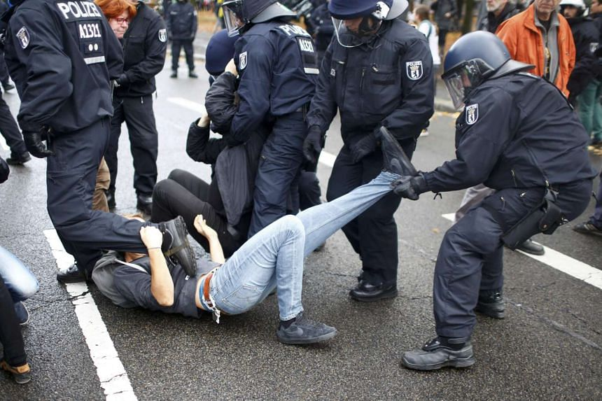 Police move away people who are blocking the street in protest at the right-wing demonstration.