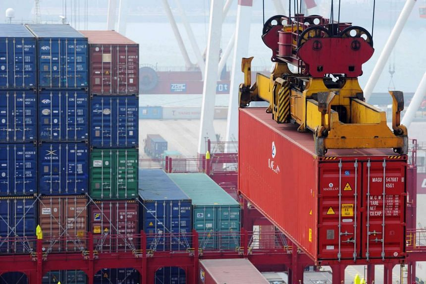 Cargo containers being moved about in Qingdao port, in eastern China's Shandong province, on Oct 13, 2015.
